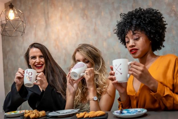 Multi-etnische levensstijl van drie vriendinnen met koffie