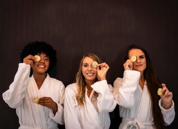 Multi-etnische levensstijl van drie vriendinnen plezier in een schoonheidssalon met witte jassen