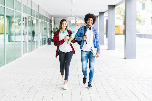Multi etnische mannelijke en vrouwelijke studenten die samen in universitaire campus lopen