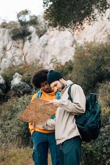 Multi-etnische mannelijke wandelaar die de bestemming op kaart in het bos vinden