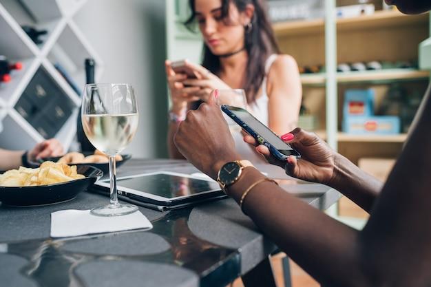 Multi-etnische meisjes die en met smartphone drinken babbelen