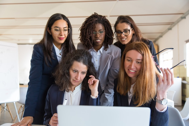 Multi-etnische onderneemsters die laptop in bureau met behulp van