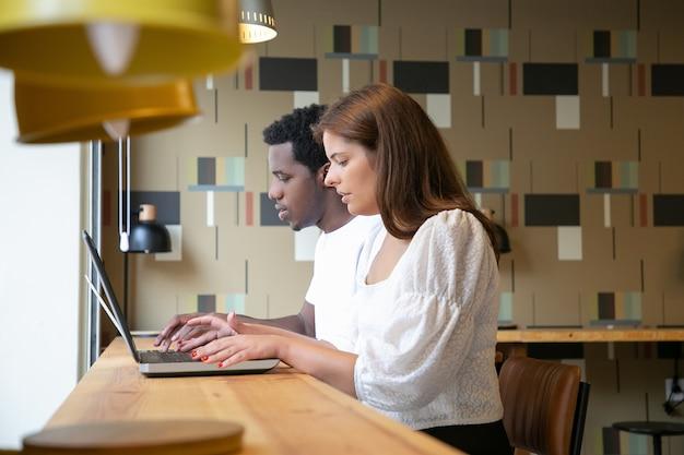 Multi-etnische ontwerpers zitten samen en werken op laptops in coworking space