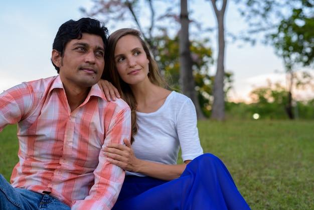 Multi-etnische paar zitten en denken op de weide