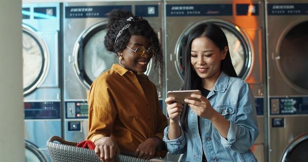 Multi-etnische stijlvolle jonge meisjes praten en kijken naar foto's of video op smartphone. vrienden staan in de wasservice. afro-amerikaanse en aziatische vrouwen met telefoon terwijl wasmachines werken.