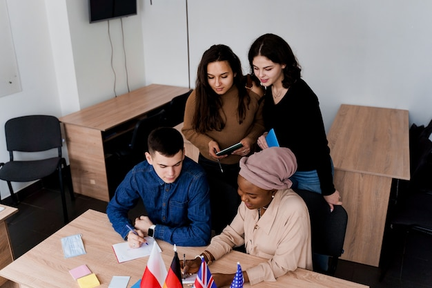 Multi-etnische studenten en docenten studeren samen vreemde talen in de klas.