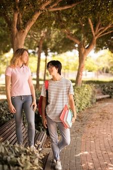 Multi-etnische tienervrienden die in park wandelen