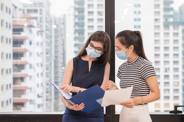 Multi etnische twee jonge bedrijfscollega die gezichtsmasker draagt