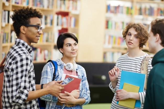 Multi-etnische universitaire studenten die in bibliotheek spreken