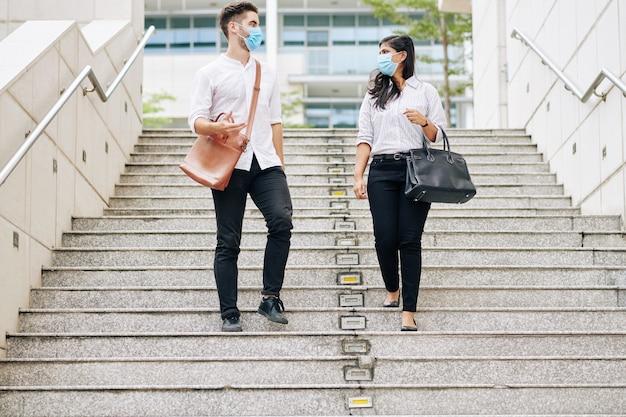 Multi-etnische universiteitsstudenten met beschermende maskers lopen de trap af en bespreken lessen