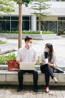 Multi-etnische universiteitsstudenten met medische maskers die tijd doorbrengen op de campus en aan projecten werken