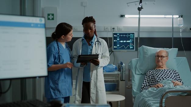 Multi-etnische verpleegster en arts kijken naar tablet voor tests