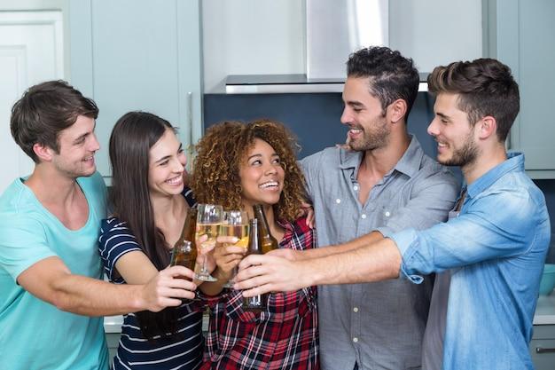 Multi etnische vrienden die bier en wijn in keuken roosteren
