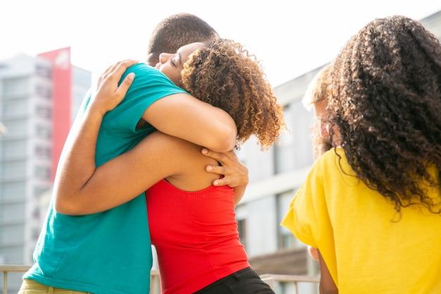 Multi-etnische vrienden die elkaar in openlucht begroeten