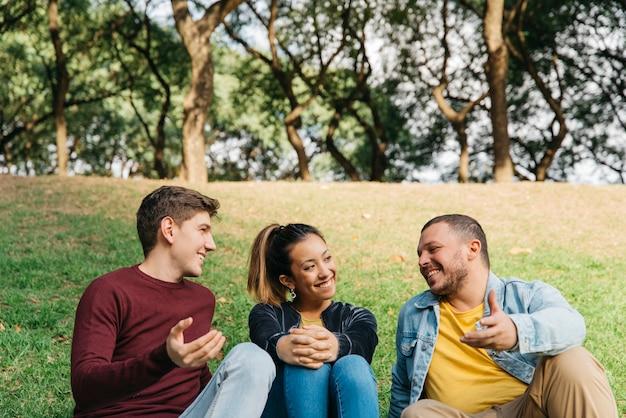 Multi-etnische vrienden die en op gras in park spreken zitten