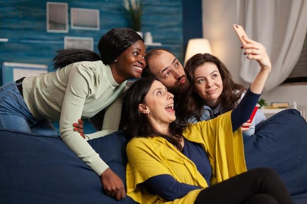 Multi-etnische vrienden die grappige gezichten trekken terwijl ze selfie-foto's maken in appartement, bier drinken. groep diverse mensen lachen, zittend op de bank 's avonds laat in de woonkamer.