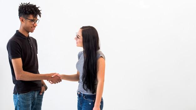 Multi-etnische vrienden die handen op witte oppervlakte schudden