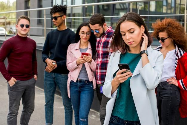 Multi-etnische vrienden die mobiele telefoon met behulp van in openlucht