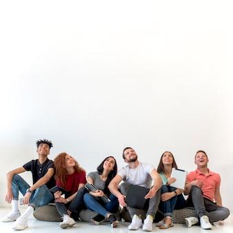 Multi-etnische vrienden die op vloer zitten die omhoog tegen witte achtergrond kijken