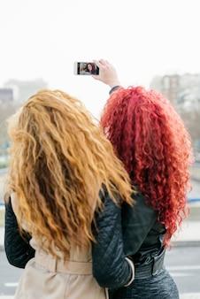 Multi-etnische vrienden die plezier hebben in de stad die selfie neemt.