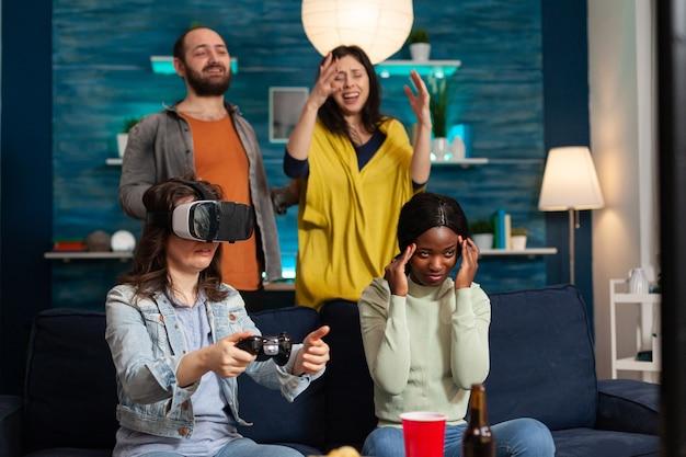 Multi-etnische vrienden die virtual reality ervaren en videogames verliezen met een vr-headset tijdens gamecompetitie. gemengd ras groep mensen die samen rondhangen en 's avonds laat plezier hebben in de woonkamer