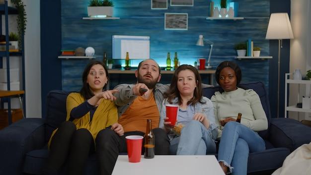 Multi-etnische vrienden veranderen van kanaal met behulp van de afstandsbediening op televisie tot ze 's avonds laat een komische film vinden terwijl ze op de bank zitten tijdens een thuisbioscoopfeest. groep multiraciale mensen die samen van tijd genieten