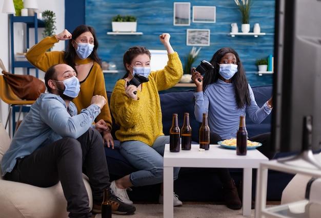 Multi-etnische vrienden vieren de overwinning terwijl ze videogames spelen met een gezichtsmasker en sociale afstand bewaren tijdens de wereldwijde pandemie met corona in de huiskamer die handen opsteekt.