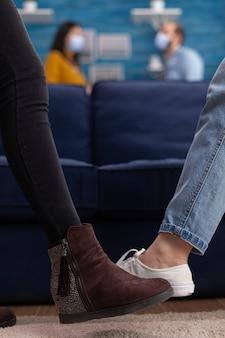 Multi-etnische vrienden zeggen hallo aanrakende voeten en houden sociale afstand tijdens de wereldwijde pandemie om het coronavirus niet te verspreiden terwijl ze plezier hebben in de woonkamer en samen tijd doorbrengen.