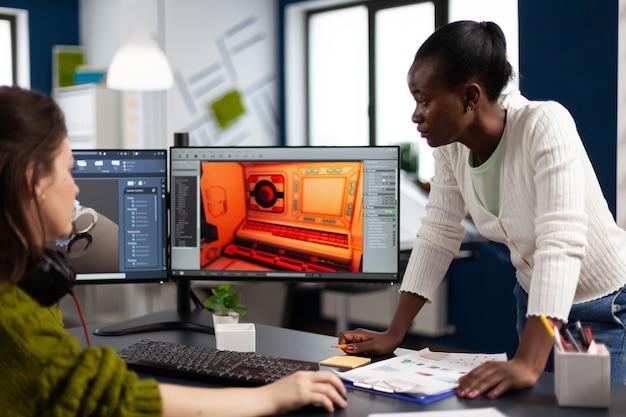 Multi-etnische vrouwelijke ontwerper die naar een computer met twee schermen kijkt