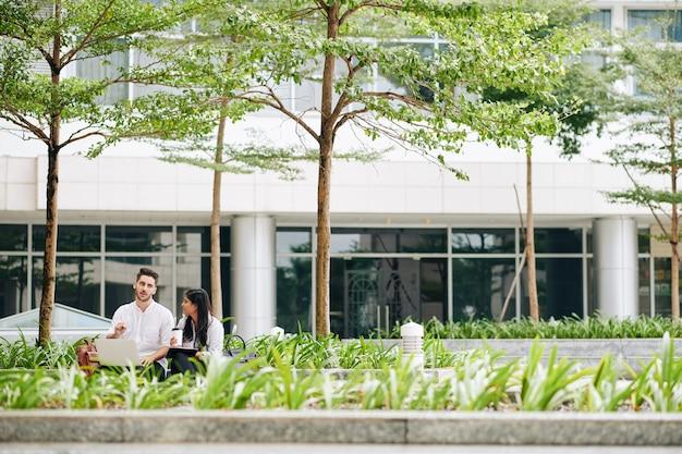 Multi-etnische zakencollega die buiten het kantoorgebouw vergadert en het project bespreekt waaraan ze werken