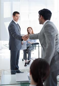 Multi-etnische zakenlieden handen schudden