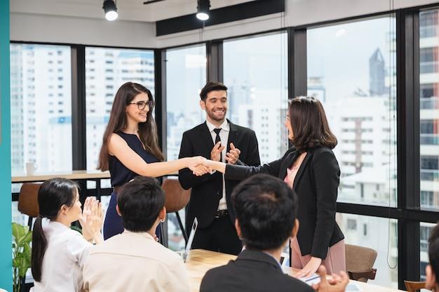 Multi-etnische zakenvrouw handen schudden met overeenkomst zakelijke samenwerking en collega's feliciteren in moderne kantoren