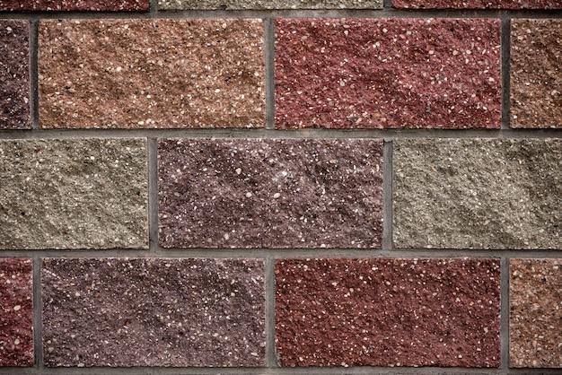 Multi gekleurde bakstenen gerangschikt in rijen op de muur