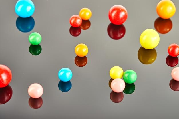 Multi gekleurde ballen van kauwgom op een grijze achtergrond met bezinning.