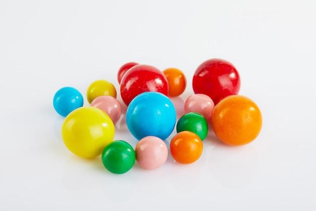 Multi gekleurde ballen van kauwgom op een witte achtergrond met bezinning.