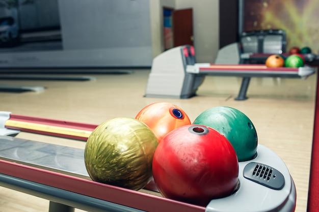 Multi-gekleurde bowlingballen liggen op de plank in de bowlingclub.