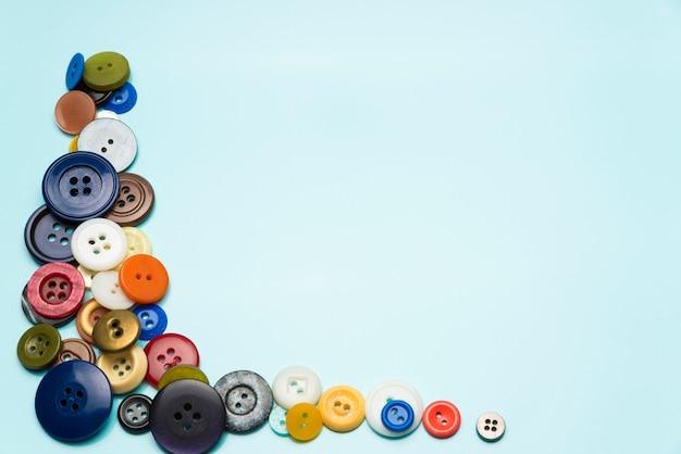 Multi-gekleurde knoppen liggen op een blauwe achtergrond.