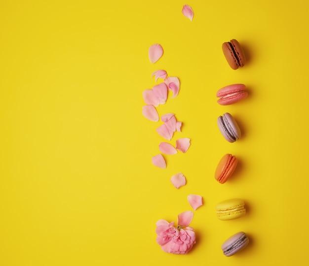 Multi gekleurde macarons met crème en een roze roos knop met verspreide bloemblaadjes