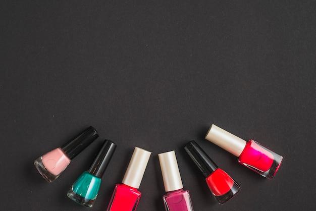 Multi gekleurde nagellakflessen die krommevorm op zwarte achtergrond vormen