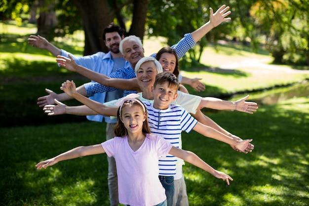 Multi generatie familie staan in een rij met uitgestrekte armen