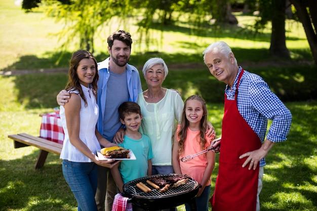 Multi generatie familie staande in de buurt van de barbecue in park