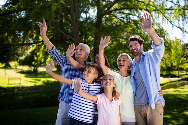 Multi generatie familie zwaaien hand in de lucht in het park