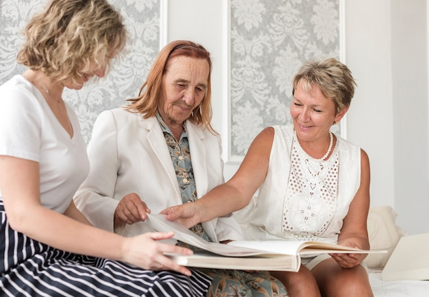 Multi generatie vrouwen op zoek oude foto-album tijdens de vergadering op de sofa