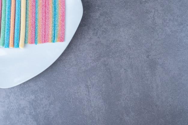 Multicolor gummy snoepjes op een bord op marmeren tafel.