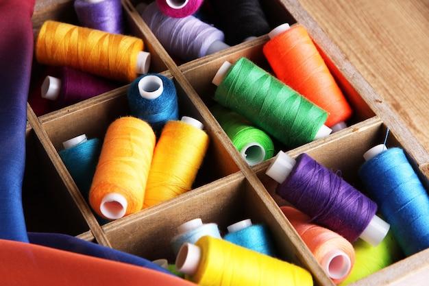 Multicolor naaigaren in houten doos, op houten achtergrond, close-up