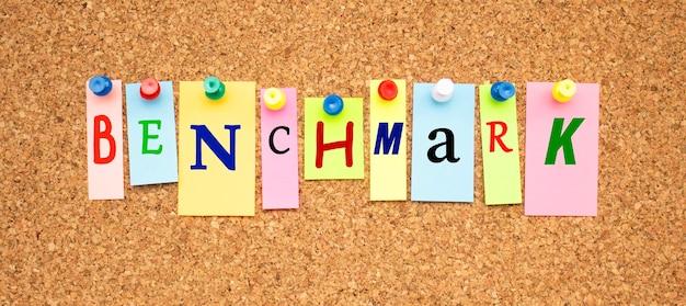 Multicolor notities met letters vastgemaakt op een bord van kurk word benchmark