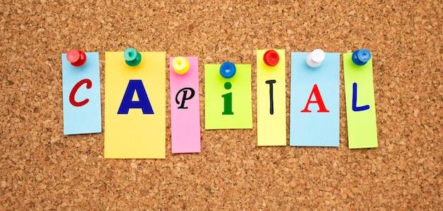 Multicolor notities met letters vastgemaakt op een bord van kurk word capital