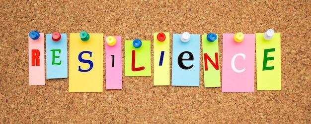 Multicolor notities met letters vastgemaakt op een bord van kurk word resilience