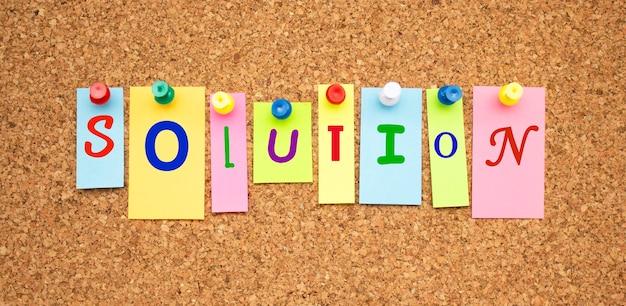 Multicolor notities met letters vastgemaakt op een prikbord kurk