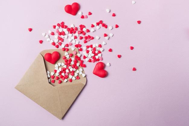 Multicolor snoep suiker snoep harten vliegen uit ambachtelijke papieren post envelop. happy valentine's dayconcept. feestelijke achtergrond